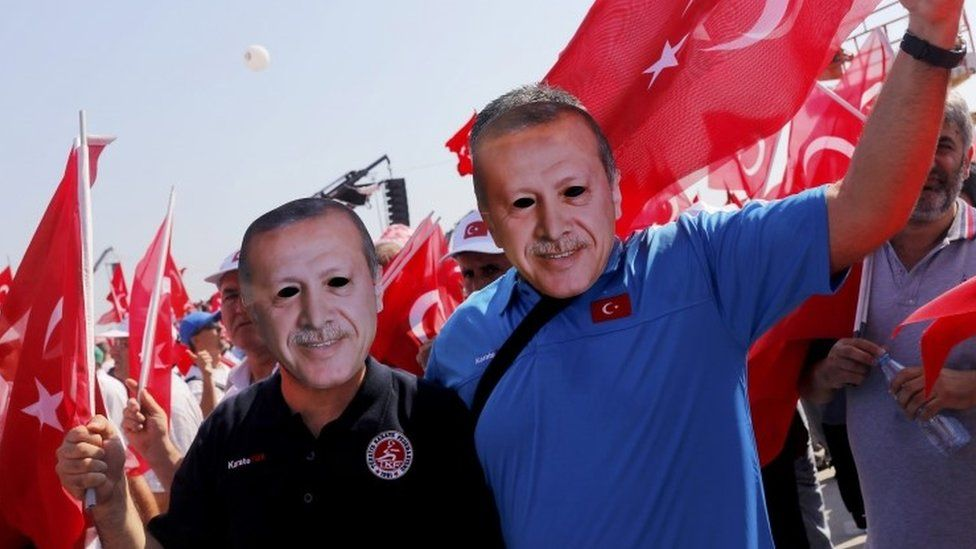 Istanbul anti-coup rally supporters wear Erdogan masks
