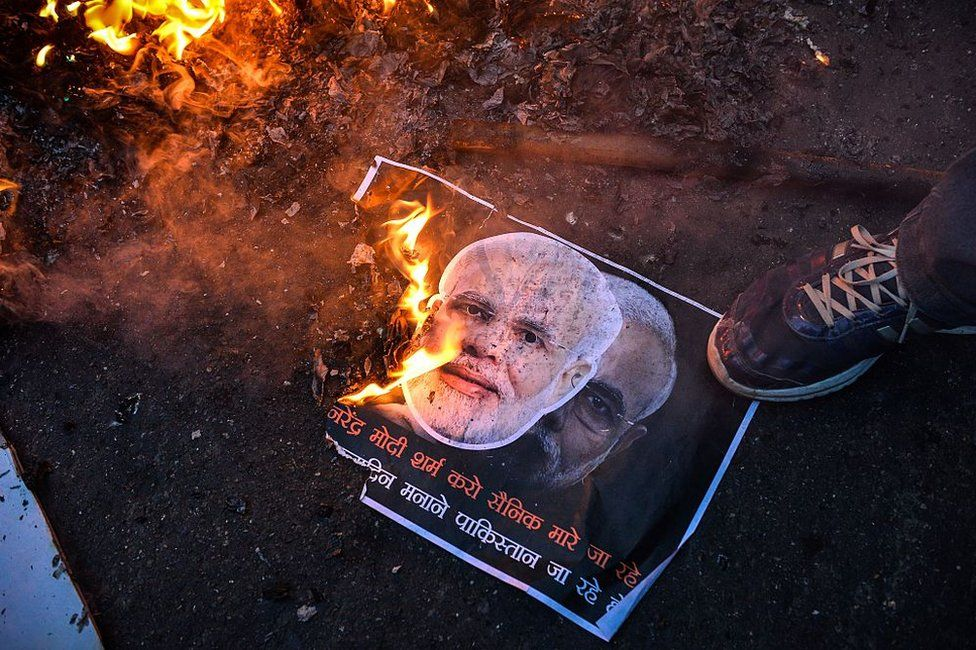 Activists of the Indian Youth Congress burn a poster with images of Indian prime minister Narindra Modi and Pakistan prime minister Nawaz Sharif during Modi's visit to Pakistan, on December 25, 2015