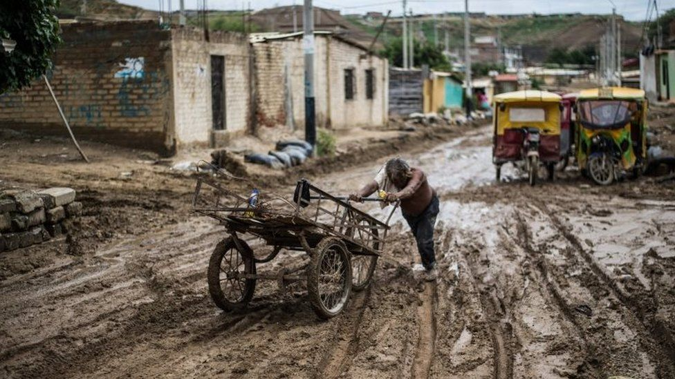 A local resident pushes his cart through the mud after the flooding caused by recent rains, in the province of Paita in Piura, northern Peru, on March 24, 2017.