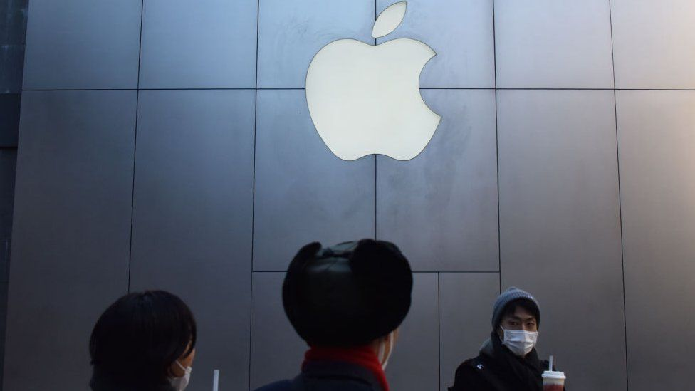 People stand in front of an Apple store in China