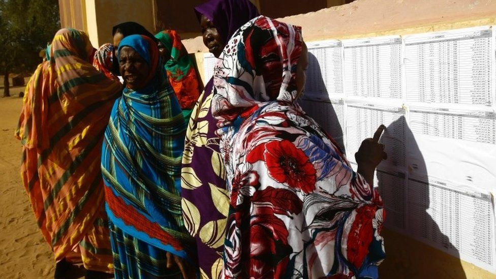 Women check their names on ballot papers at a polling station at the Abu Shouq camp for Internally Displaced Persons