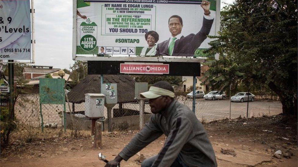 A man rides a bicycle by a presidential campaign billboard of Zambian incumbent president and leader of Zambian ruling party Patriotic Front Edgar Lungu two days ahead of Zambian Presidential and legislative elections on August 8, 2016