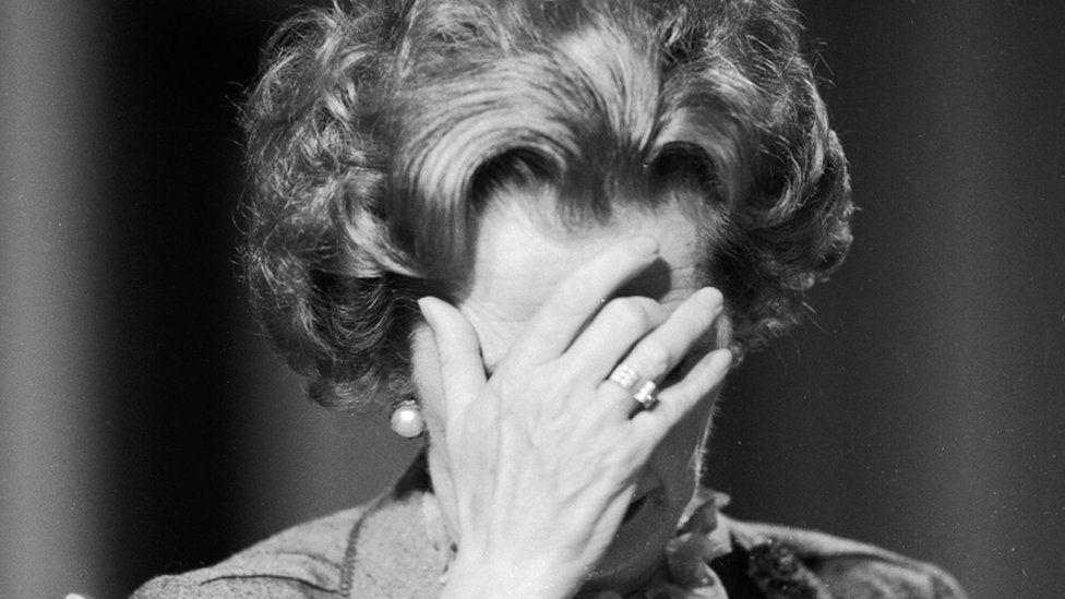 Margaret Thatcher with her head in her hands
