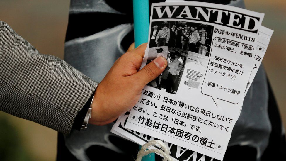 A man holds leaflets denouncing South Korean boy band BTS outside Tokyo Dome