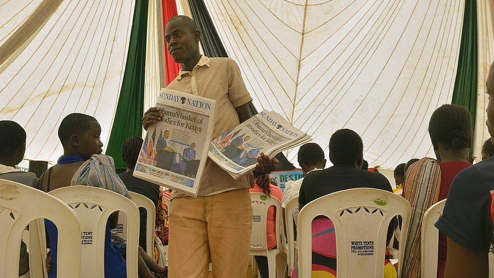 A newspaper vendor hawks copies of the daily edition with a headline photo of visiting US President Barack Obama with his host Kenyan President Uhuru Kenyatta, on July 26, 2015 in the village of Kogelo in Siaya county, where residents had gathered to watch a televised live broadcast of Obama's speech