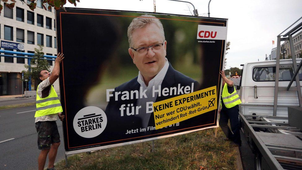 Workers take down an election campaign poster showing Frank Henkel, top CDU candidate on 18 September 2016 in Berlin.