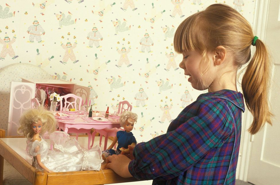 Girl playing with Barbie