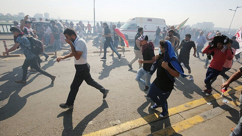 Iraqi protesters run for cover as security forces use tear gas to disperse the crowd in central Baghdad during anti-government demonstrations in the Iraqi capital on October 25, 2019