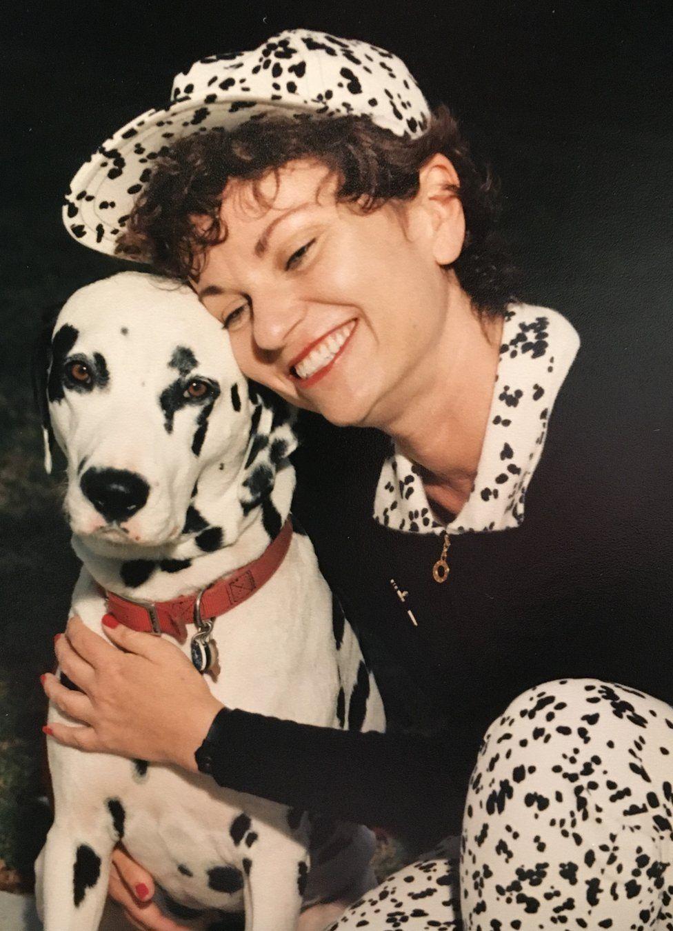 Cat Hulbert cuddling a dog, wearing spotty trousers and matching baseball cap