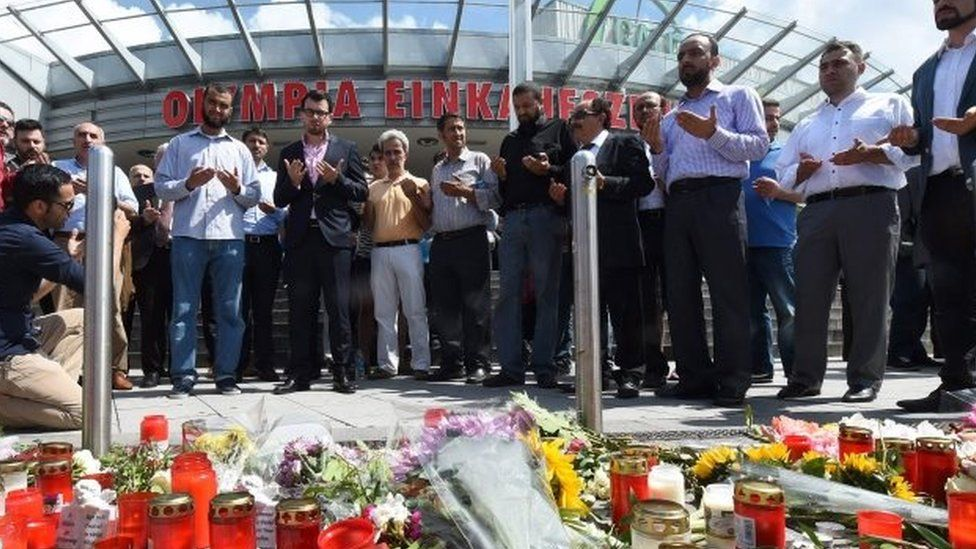 People pray at a memorial of candles and flowers in front of the Olympia shopping centre in Munich where Friday's shooting happened (24/07/2016)