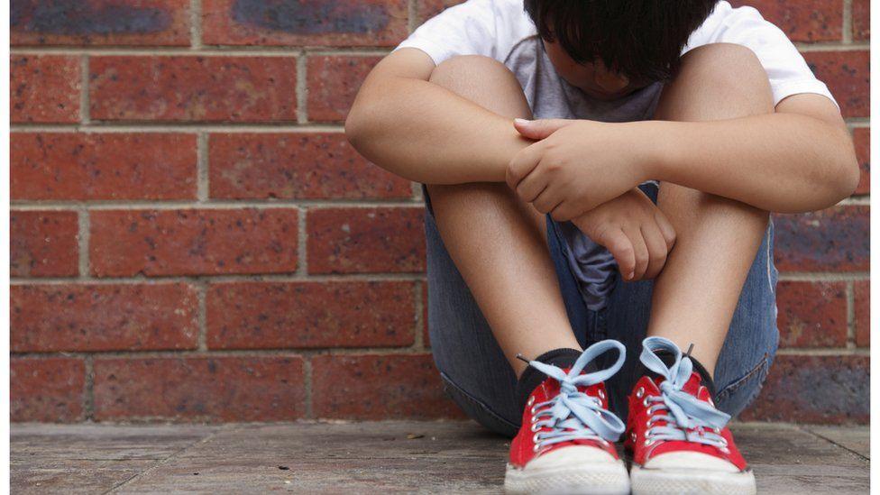 Boy sitting against a brick wall with his head down