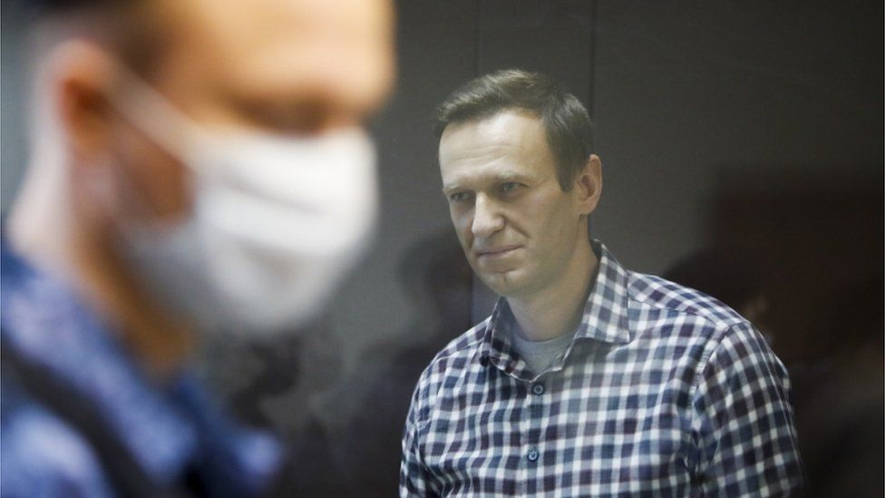A masked police officer stands in front of Alexei Navalny during a court hearing in February 2021