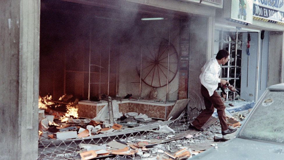 A man with a pair of shoes in his left hand runs out of a destroyed shoe store on February 27, 1989