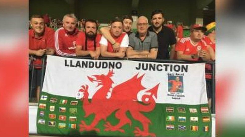 Brad Evans and fellow Wales fans from Llandudno Junction with the flag that's travelled to every Wales match