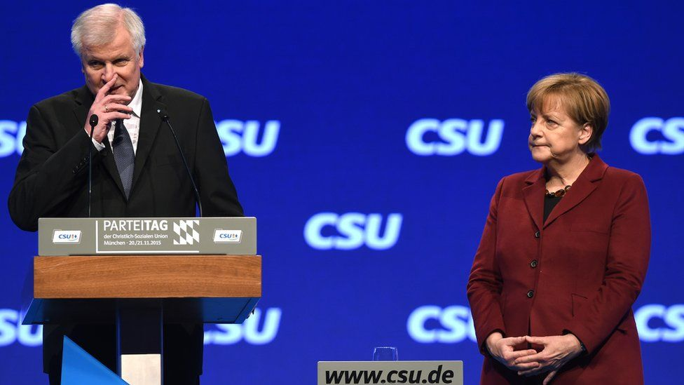 Horst Seehofer addresses the CSU congress on 20 November while Chancellor Angela Merkel stands to his side on the stage.