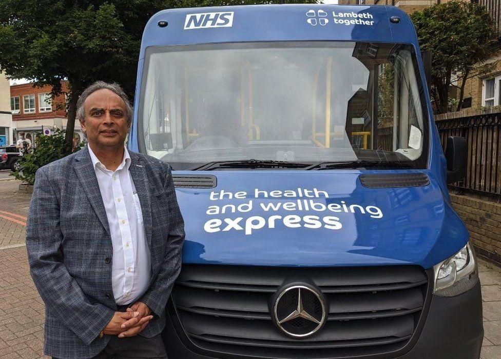 Ash Soni posing next to NHS bus