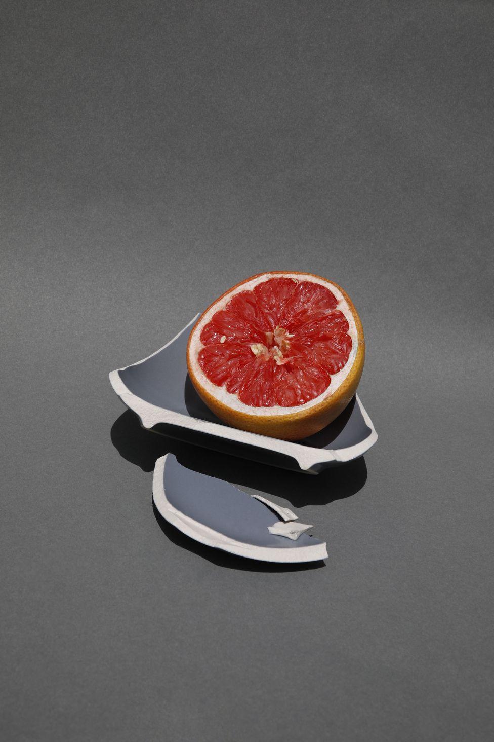 Half an orange in a broken bowl