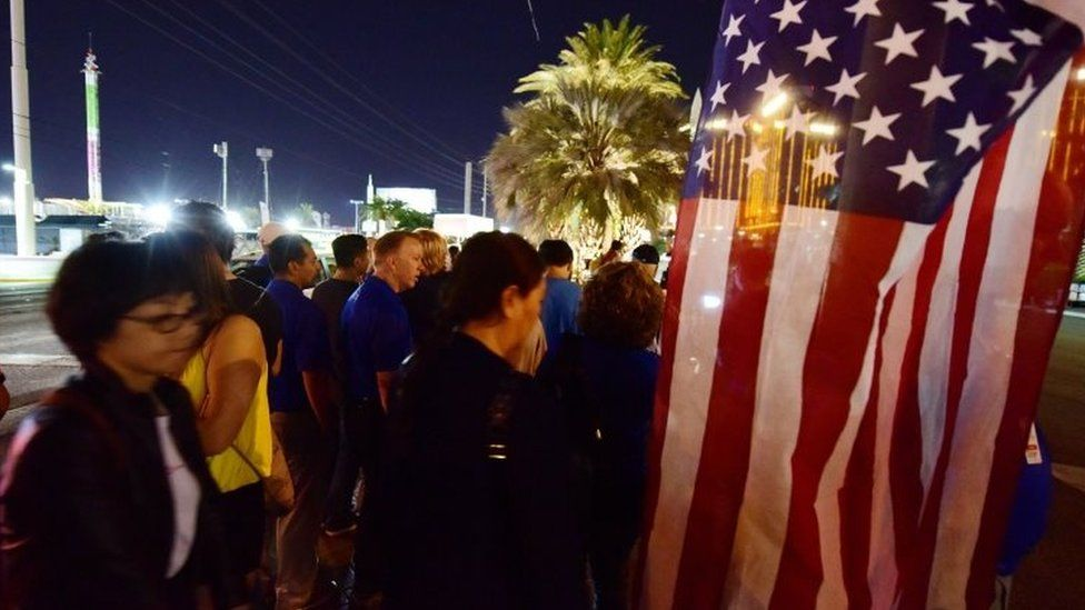 People look on near a US national flag at a makeshift memorial near the Mandalay Hotel on the Las Vegas Strip (03 October 2017)
