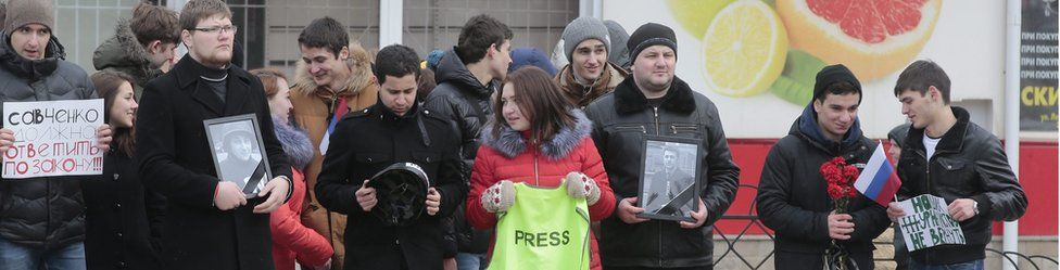 Russian protesters holding portraits of killed Russian TV journalists (21 March)