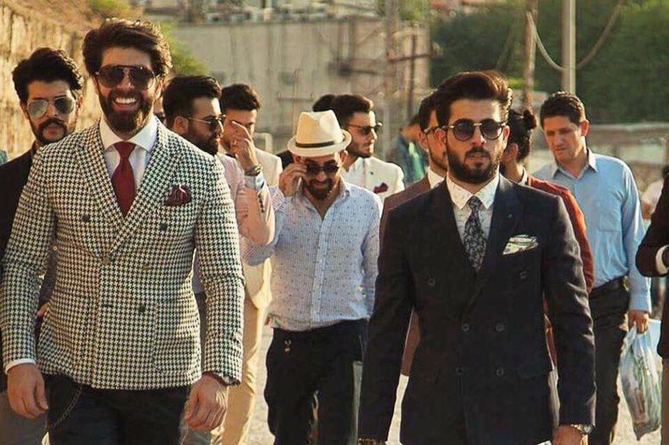 Iraqi men walking down a street in suits