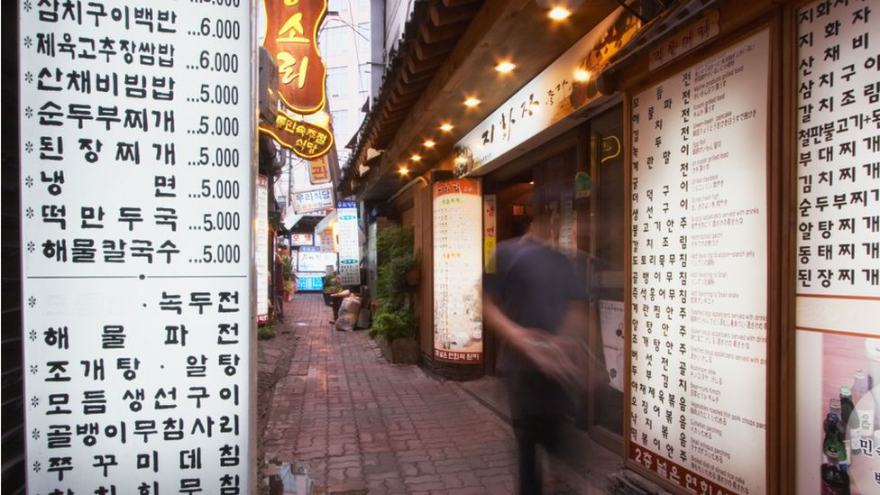 A man walking past a Korean restaurant with large menu boards outside in Seoul