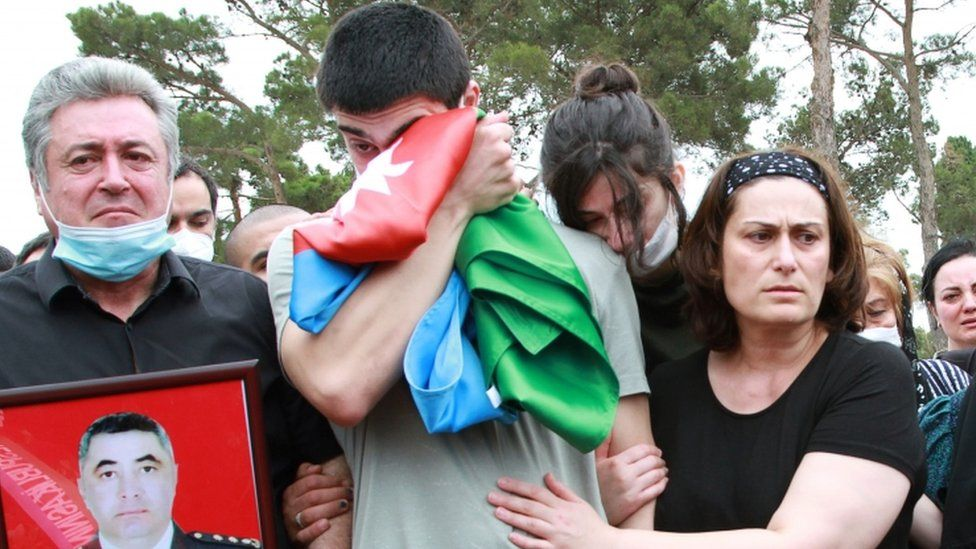 Mourners gather at the grave of an Azeri killed in border fighting with Armenia