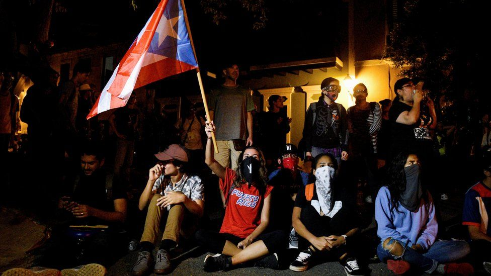 Demonstrators sit in to block the exit of Pedro Pierluisi's convoy after his first news conference as governor of Puerto Rico