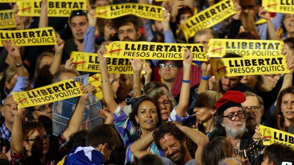 """People hold banners reading """"Freedom political prisoners"""" at a protest in support of detained Catalan ex-ministers in Barcelona"""
