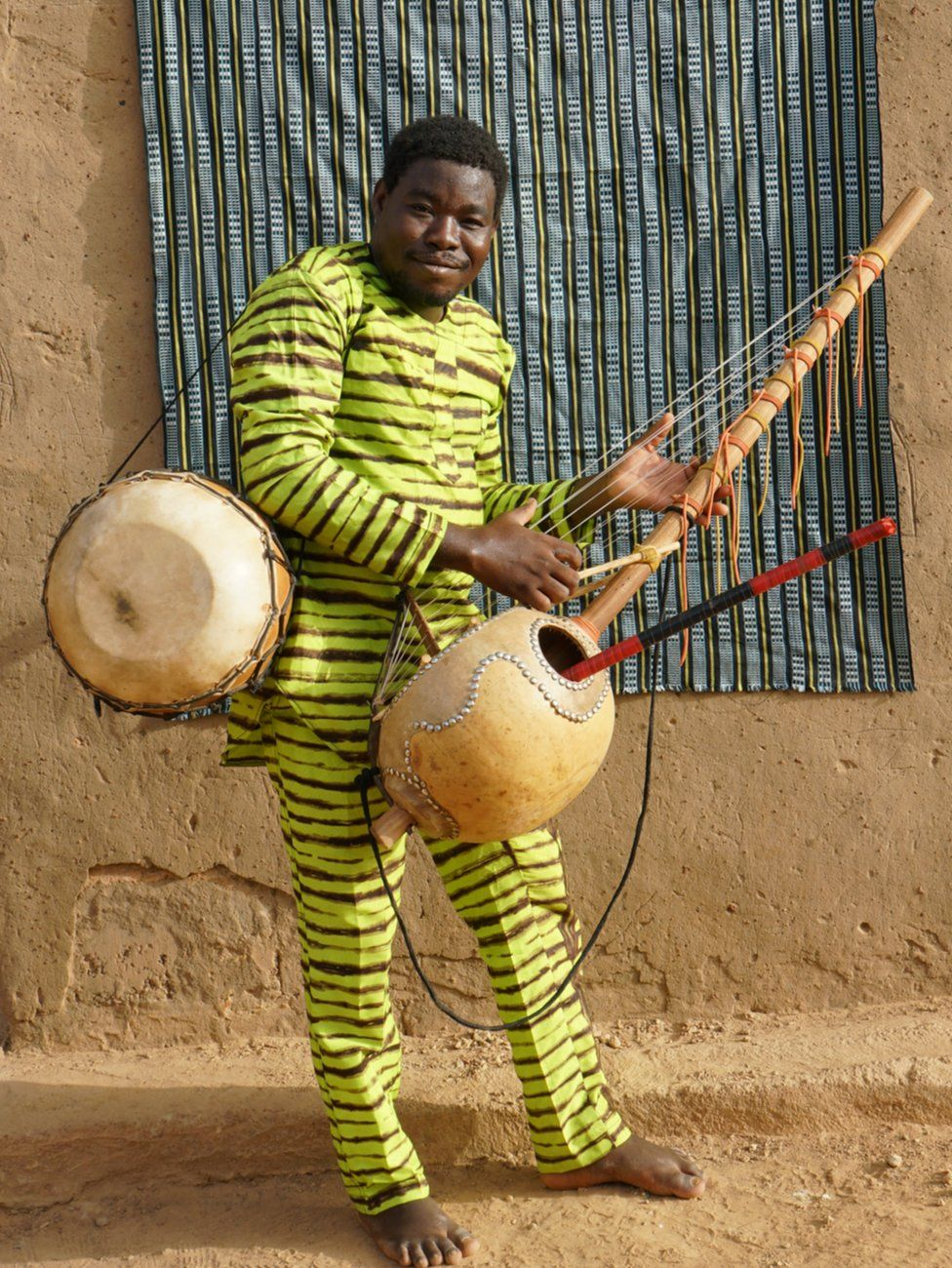 """Maboudou Sanou poses with a bendré drum, a harp-like instrument known as the kora and his flute – the three instruments he plays in Fujiie's opera. Like many musicians from griot families, and in the group itself, Sanou plays many instruments, describing himself as """"polyvalent."""""""