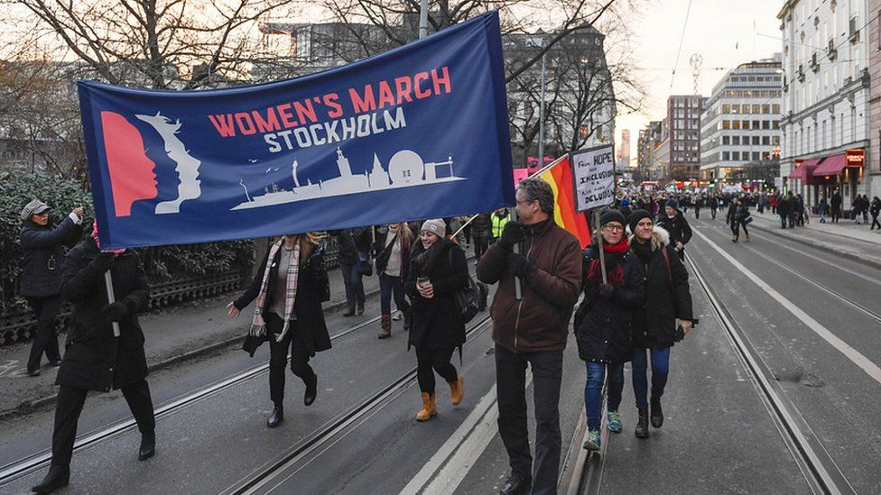 Protesters carrying banners and placards take part in a Women's March in Stockholm, Sweden, on 21 January