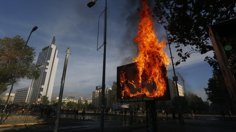 Demonstrators light fires as clashing with riot police during a protest on October 21, 2019 in Santiago, Chile