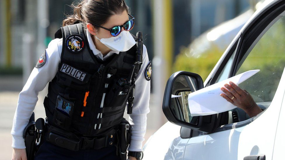 A French police officer looks at a piece of paper held by a motorist at a checkpoint on the Promenade des Anglais in Nice (6 April 2020)