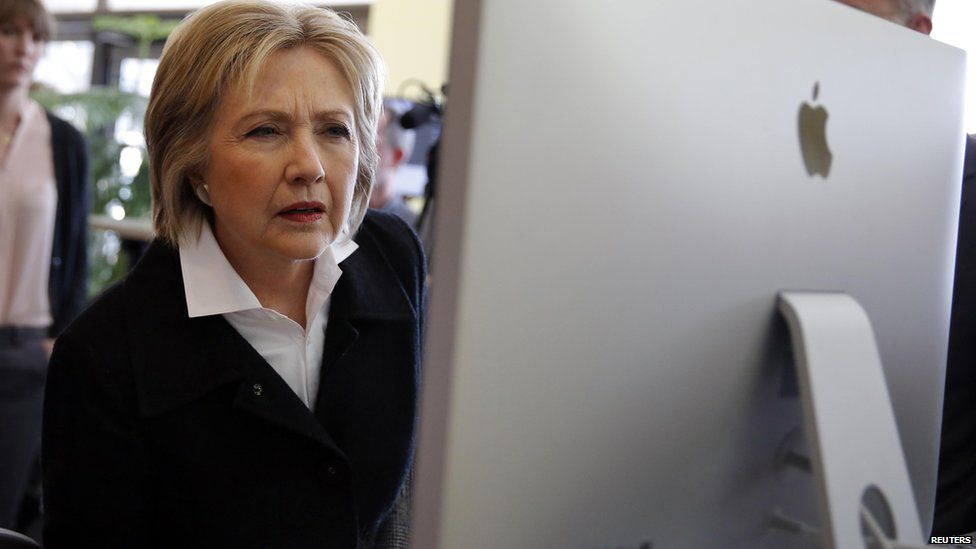 Hillary Clinton looks at a computer screen during a campaign stop in Iowa