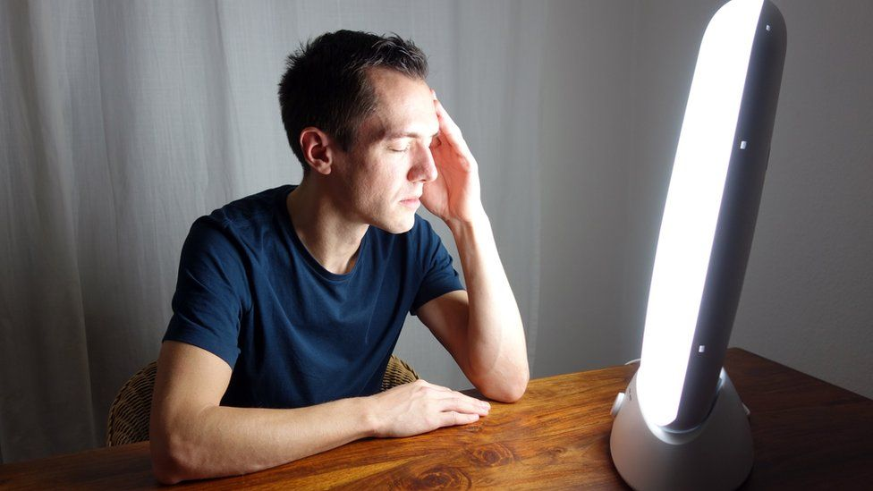 Man in front of a light box