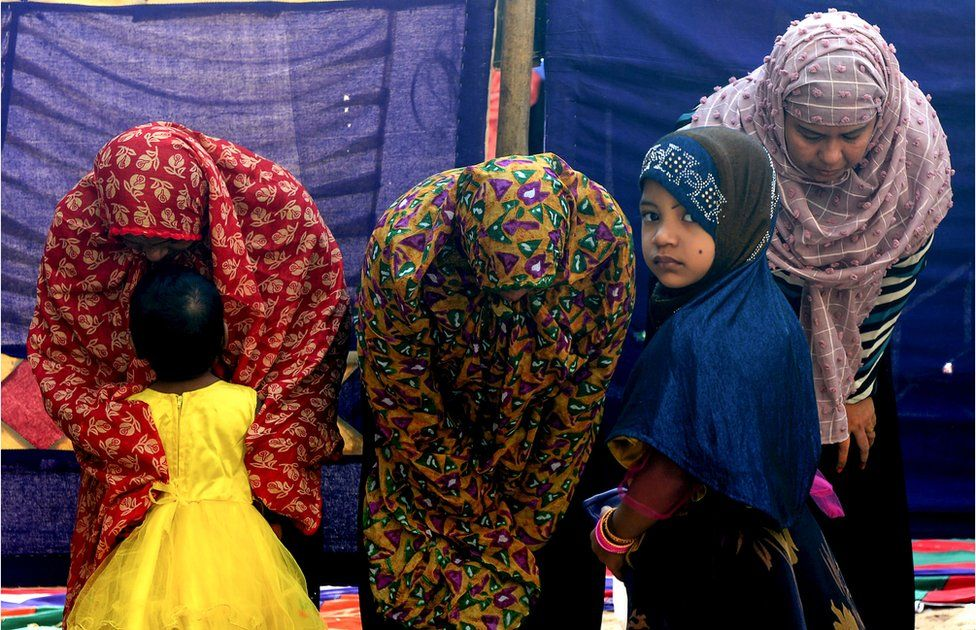 A child looks on as women offer Eid al-Adha prayers