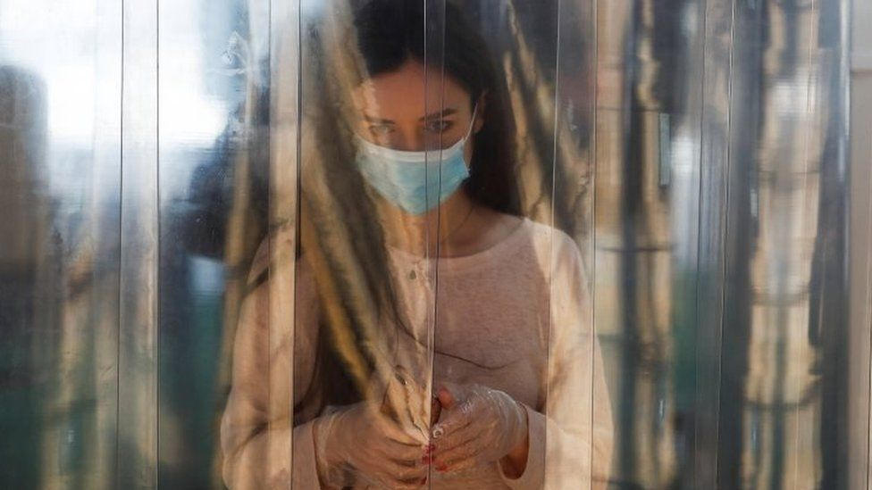 A woman wearing a protective face mask and gloves walks through a disinfection cabin at the entrance to a shopping centre in Moscow, Russia. Photo: 5 June 2020