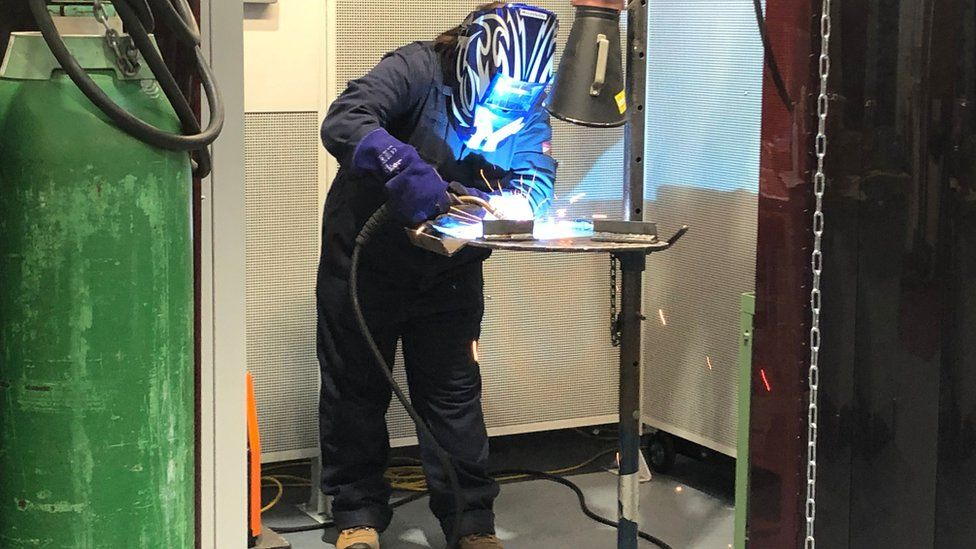 Woman welding in protective gear