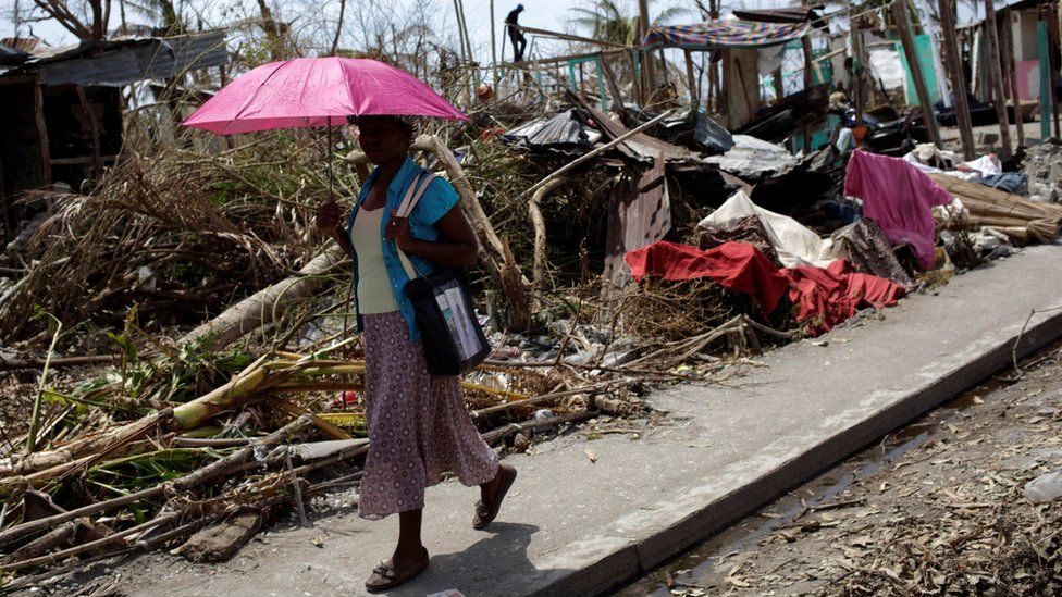 A woman holds an umbrella as she walks next to houses destroyed by Hurricane Matthew in Les Anglais