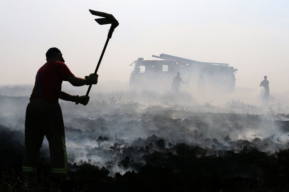 Firefighters beat out wildfires on Winter Hill near Rivington in Lancashire, north west England on 1 July 2018.
