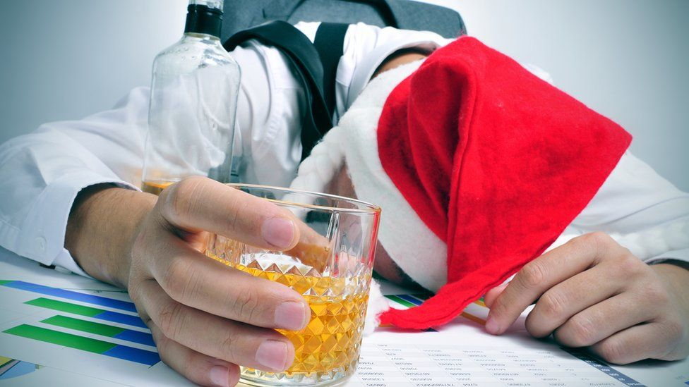 Man with drink sleeping at desk after Christmas party