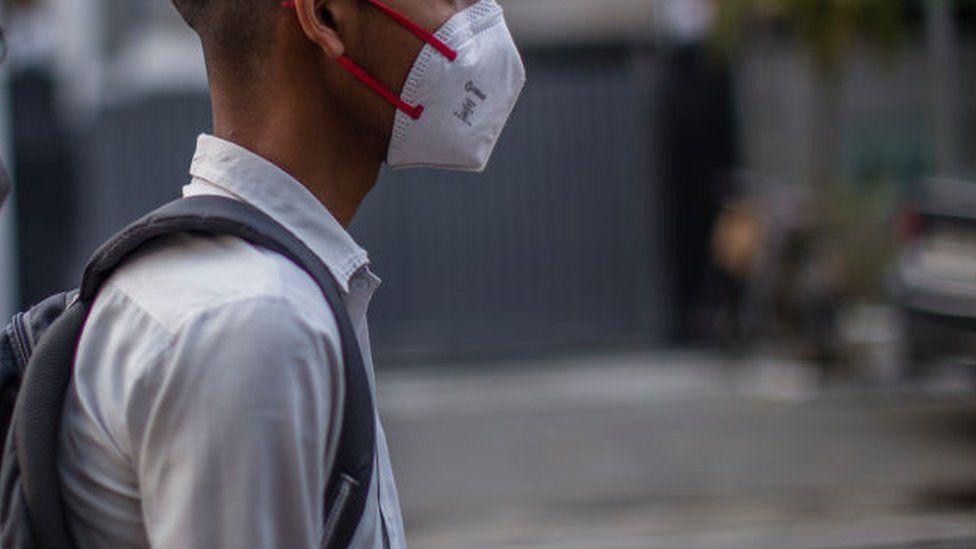 A Delhi school boy with a shoulder bag looks on