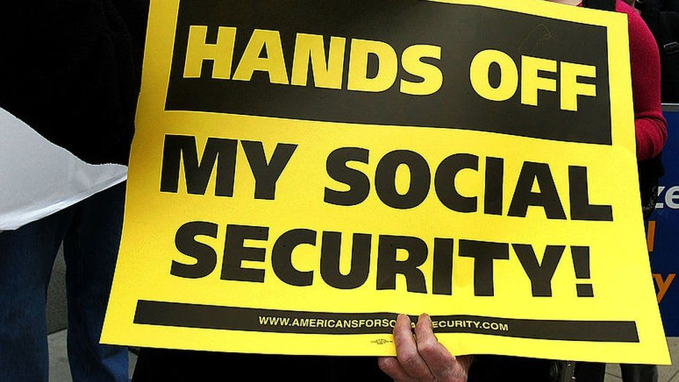 Bob Ducharme participates displays a sign during a demonstration in front of the Social Security Administration office