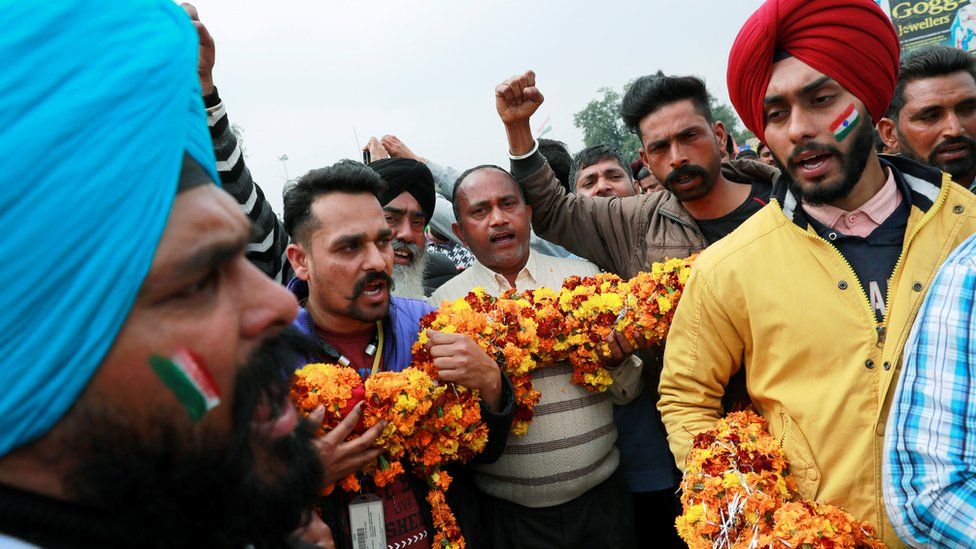 People hold a garland as they shout patriotic slogans before the arrival of Indian Air Force pilot, who was captured by Pakistan on Wednesday, near Wagah border, on the outskirts of the northern city of Amritsar, India, March 1, 2019