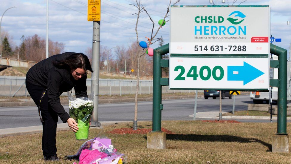 A woman places flowers outside Residence Herron, a care facility where 31 people have died