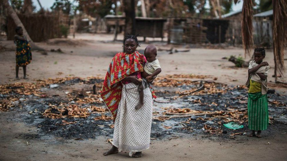 Woman and child amid burned buildings