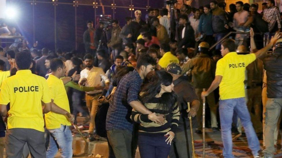 Man helps a woman during unrest in Bangalore (31 Dec 2016)