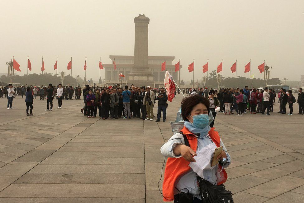 People visit Tiananmen Square as a sandstorm hits Beijing, China 4 May 2017.