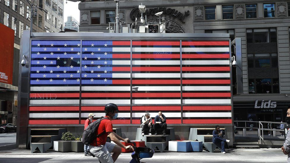 People are seen by the American flag in Times Square on May 22 in New York City