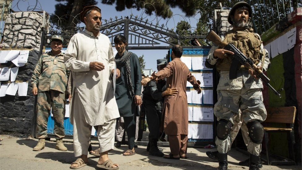 Security forces search voters as they enter a polling station in Kabul