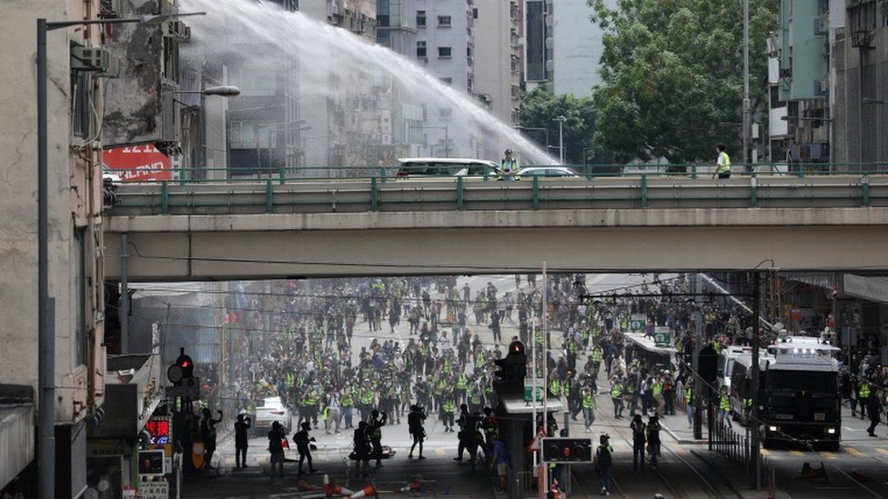 Police water canon trucks spray water to disperse protesters during a rally against the implementation of a new national security law in Causeway Bay, Hong Kong, China, 24 May 2020